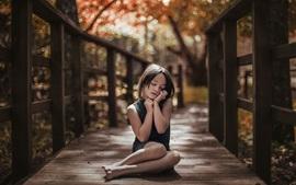 Симпатичная девочка сидит на деревянном мосту, думая