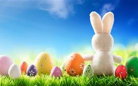 Ovos de Páscoa coloridos, grama, coelho branco, céu azul