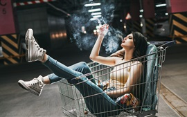 Girl sit in shopping cart, jeans, cigaret