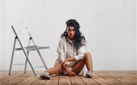 La muchacha se sienta en el piso, pelo rizado, silla