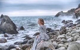 Lonely girl, stones, sea