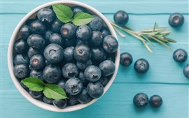One bowl of blueberries, wood table