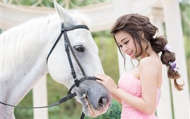 Hermosa chica asiática, falda rosa, caballo