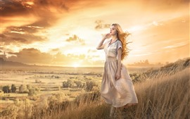 Preview wallpaper Beautiful blonde girl, grass, mountain, wind
