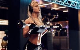 Garota loira, fitness, esporte, fones de ouvido, halteres, ginásio