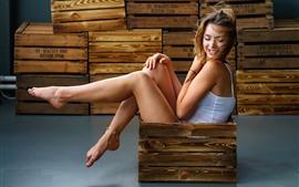 Sonrisa niña sentada en caja de madera