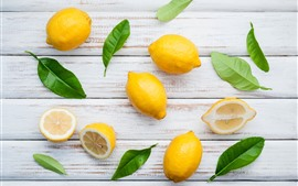 Некоторые лимоны, зеленые листья, древесная плита