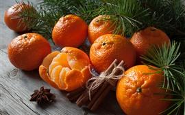 Algunas mandarinas, canela, ramas de pino