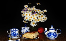 Flores de camomila branca, bule, xícara, pão, maçã, fundo preto