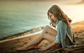금발 소녀 해변, 모래에 앉아