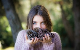 Preview wallpaper Brown hair girl, sweater, hands, pine cone