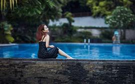Menina sente-se no lado da piscina