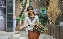 Preview wallpaper Happy Chinese girl riding bike, flowers