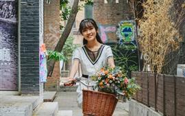 Happy Chinese girl riding bike, flowers