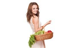 Sourire fille regarder en arrière, panier, légumes, fond blanc