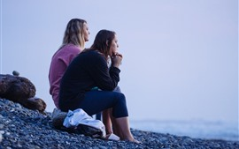 Preview wallpaper Two girls look at sea, coast, stones