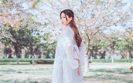 Vestido blanco niña mira hacia atrás, estilo retro, primavera, flores del árbol