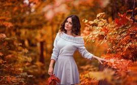 Chica de cabello castaño en otoño, suéter, hojas de arce.