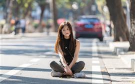 Niña china de pelo largo sentada en el suelo