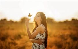 Chica de pelo largo, mariposa, sol.