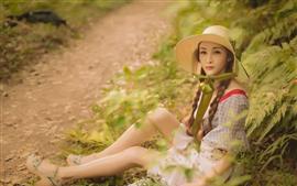 Menina sente-se no chão, chapéu, natureza