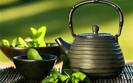 Chaleira, xícara de chá, folhas de hortelã