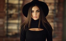Chica de pelo largo, vestido negro y sombrero.