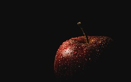 Red apple, water droplets, darkness