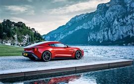 Vista lateral del auto rojo Aston Martin, río, montañas