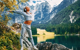 Blonde girl, fitness, headphones, mountains, lake, morning