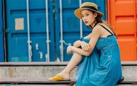 Menina chinesa, saia da sarja de Nimes, chapéu, sente