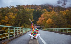 Preview wallpaper Colorful sweater girl, pose, sit on ground, bridge, trees, autumn