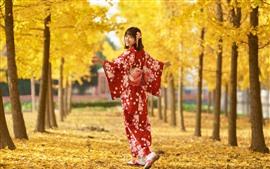 Menina japonesa olhar para trás, sorrir, quimono vermelho, árvores, folhas amarelas, outono