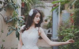 Linda menina asiática, saia branca, obscuro