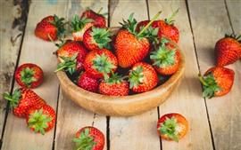 Un tazón de fresa madura, mesa de madera