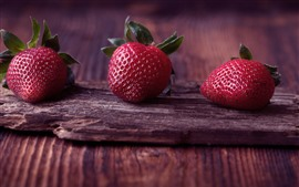 Preview wallpaper Three strawberries, fruit, wood