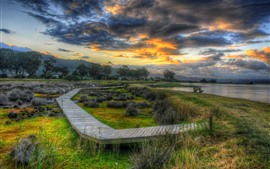 Preview wallpaper Wooden bridge, coast, river, trees, grass, clouds, dusk