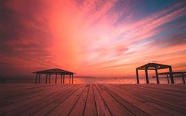 Playa, mar, tablero de madera, puesta de sol, cielo rojo.