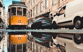 Calle de la ciudad, tranvía, coches, agua.