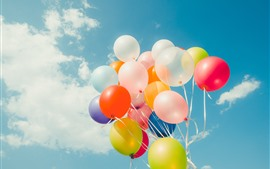 Colorful balloons, blue sky, white clouds