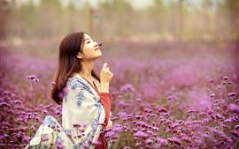 Feliz chica China, flores rosas, primavera
