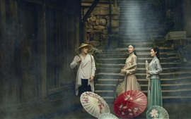 Meninas e homem retros do estilo, guarda-chuva, névoa, vila