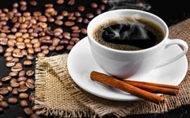 Una taza de café, canela, granos de café.