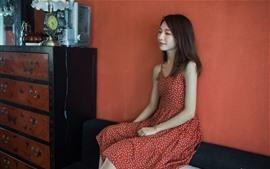 Saia vermelha menina asiática, sente-se, sala