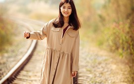Preview wallpaper Smile Asian girl walking on the railroad