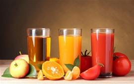 Três copos do suco de fruta, maçãs, laranjas, tomates