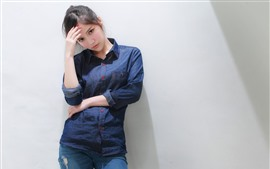 Preview wallpaper Young Asian girl, standing beside wall