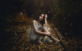 Preview wallpaper Girl sitting on ground, many leaves