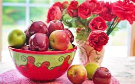 Uma bacia de maçãs vermelhas e verdes, flores vermelhas