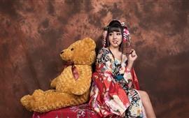 Menina japonesa do sorriso e urso de peluche, quimono